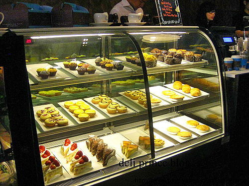 Cup cake, pastry and cheesecake are displayed in the fridge.
